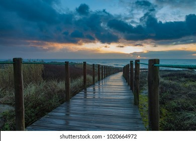 Walkway to the beach at sunset after rain.
