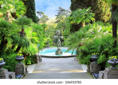 Walkway in a beautiful Park with Palms, thuyas and fountain (russia, sochi)