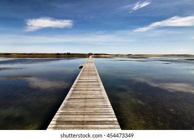 Walkway To The Dunes Wooden walkway extends over marshland toward the distant dunes and ocean In Sandwich, Massachusetts.
