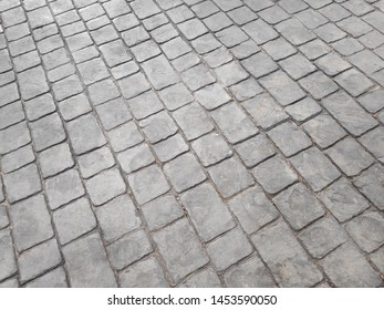 The walkway floor is made of gray square brick. Abstract background
