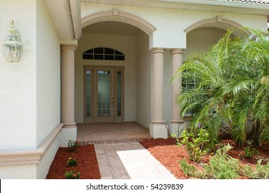 Walkway and front door to generic high end home in southwest florida with small palm tress.