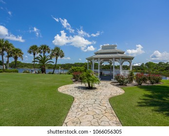 walkway to gazebo on green grass with palm trees