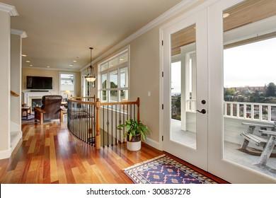 Walkway in luxury home with glass doors, and indoor balcony.