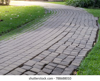 The walkway is made of brick in the lawn.