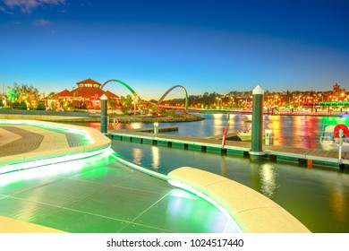 Walkway with night lighting at popular tourist attraction Elizabeth Quay Marina. The iconic Elizabeth Quay Bridge on Swan River illuminated at blue hour. Perth Waterfront Cityscape, WA. Copy space.