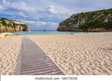 Walkway on sandy beautiful beach of Cala en Porter, Menorca island, Spain