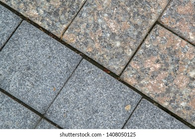 Walkway in the park made of two different kinds of flagstones (cement & granite). Diagonal. Closeup
