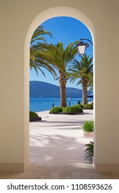 Walkway to the sea. Sunny embankment of Tivat city with green palm trees  is visible through an arch of building. Montenegro, Bay of Kotor (Adriatic Sea)