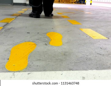Walkway signs and footsteps are painted yellow on the floor and laid down  yellow lines in the factory.