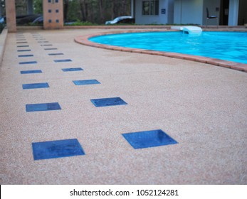 Walkway to the swimming pool which floor is made from flat tiles and stone pebble wash method for prevent slipping, Swimming pool for exercise and recreation