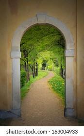 walkway through arched old door, mystical mood