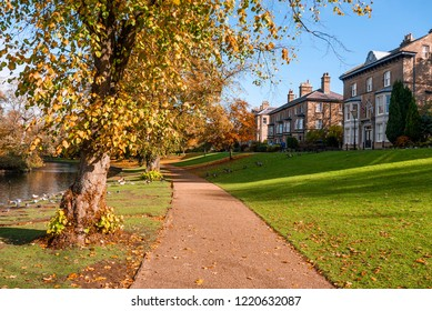 Walkway through a beautiful autumn park with stone Georgian houses and autumnal trees, taken in Buxton Park UK in fall on a sunny day.