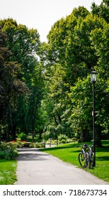 Walkway through beautiful park with summer trees and an old bicycle. Taken in Rothenburg Ob Der Tauber in Germany.