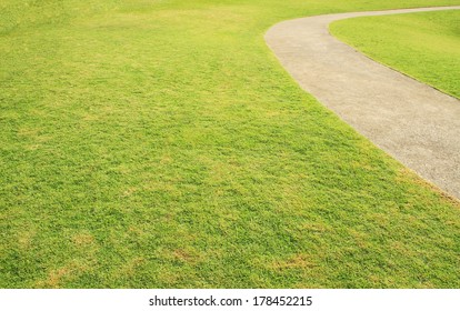 Walkway through green grass field