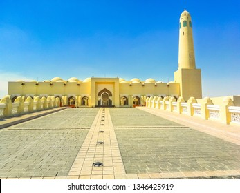 Walkway towards State Grand Mosque and minaret in a sunny day with blue sky in Doha Downtown, Middle East, Arabian Peninsula, Persian Gulf. Famous landmark in Doha West Bay.