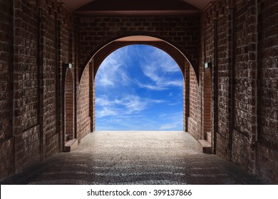 Walkway tunnel made by red brick and view of blue sky with cloud