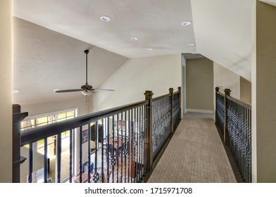Walkway upstairs with metal railings as a sky bridge above living room to bedrooms under tall vaulted ceiling.