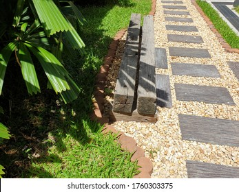 Walkway uses alternating stone and gravel stones. The side has a seat made of wood and the other side is a small garden