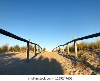 Walkway with wooden railing leading to a beach in Long Beach Island, New Jersey.