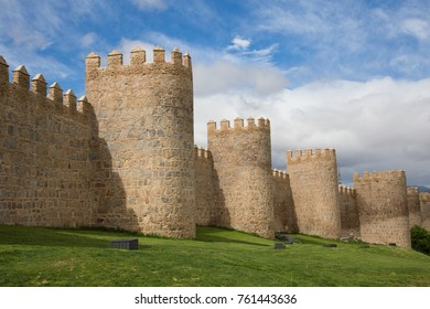 The wall of Avila, Spain. The stone wall with its turrets behind a green lawn. The picture was taken in May 2017.