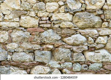 Wall with big and small, bright natural stones