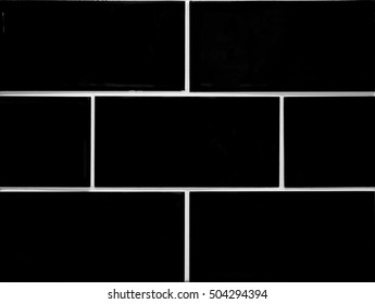 Wall of black ceramic tiles in vintage style. Home, house decoration.