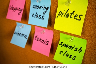 Wall board on the room of girl or lady with colorful stickers reminders activities and hobbies: pilates Spanish cooking class tennis shopping cinema
