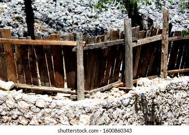 Wall built of stone. Fence made of wood. Moving perspective. Counter angle. Sunny and bright weather. Village, town, small settlement.