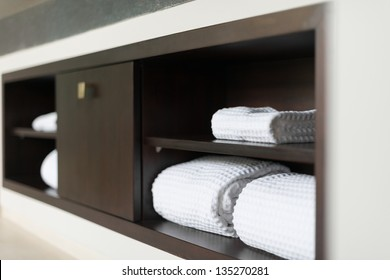 Wall with built in wooden shelf. Neat stack of white soft towels in bathroom. Closet with clean folded textile for spa and hygiene. Modern interior of hotel room. Luxury resort with classic design.
