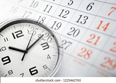 wall calendar with the number of days and white clock face closeup