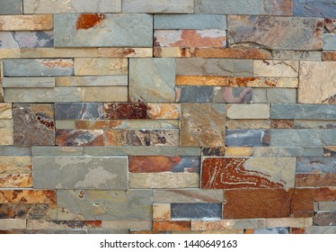 Wall cladding made of different sizes natural stone bricks. Colors are shades of red and gray. Background and texture.