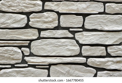 Wall cladding made of large irregular white stones on black concrete. Background and texture.