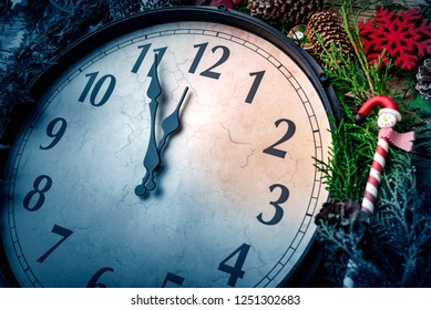Wall clock in Christmas and New Year decorations are wrapped with fir branches and Christmas decorations. On the clock five minutes to midnight.