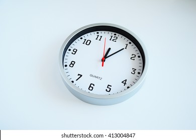 Wall clock close up isolated. White face, black clockwise and numbers, red second hand, time on the clock is 12-05. 5 minutes on clock.