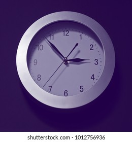 Wall clock, dial with arrows, soon three hours. Minute, hour and second hands. Round shape, shadows, hue