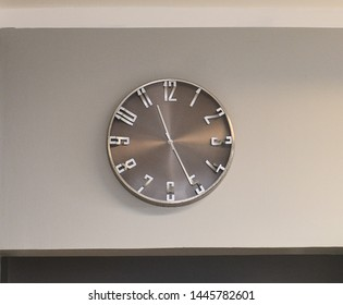 Wall clock dialing eleven and twenty-five minutes