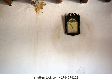 wall clock mounted on adobe wall, obsolete adobe wall,rapid flow of time, year and time,