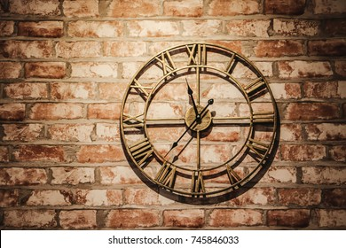 wall clock on an old brick wall, selective focus and toned image