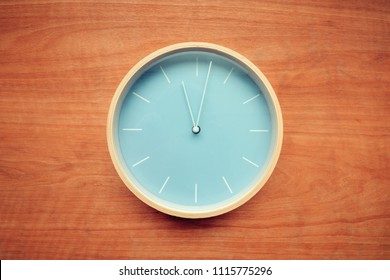 Wall clock on rustic brown wooden background