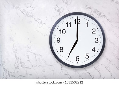 Wall clock show seven o'clock on white marble texture. Office clock show 7pm or 7am on marble background
