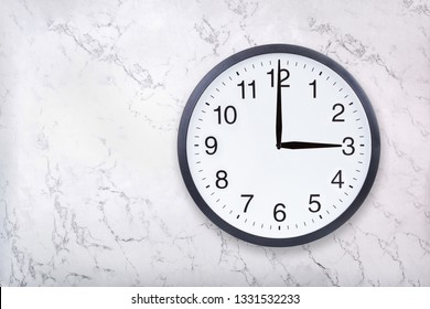Wall clock show three o'clock on white marble texture. Office clock show 3pm or 3am on marble background