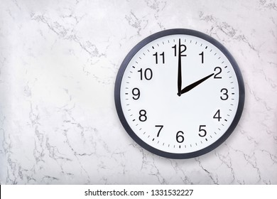 Wall clock show two o'clock on white marble texture. Office clock show 2pm or 2am on marble background