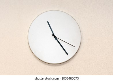 a wall clock with white face and black arrows, closeup