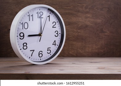 wall clock at wooden table background texture