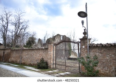 Wall with closed gate, ancient ruins, dead trees and streetlight.