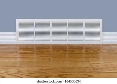 Wall cold air return grille sitting on hardwood floor