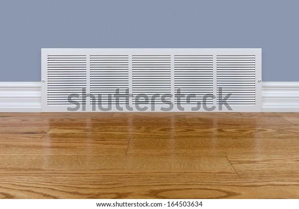 Wall cold air return grille sitting on hardwood floor