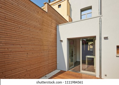Wall construction with insulating wood cladding in countryard
