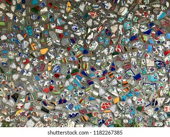 The wall is decorated with colored fragments of ceramic dishes.
