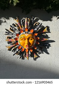 Wall decoration in the backyard with colorful facial styled ceramic while sun shines to the object on the wall and shadow at the bottom. One of the exotic style for Caribbean house or pacific home